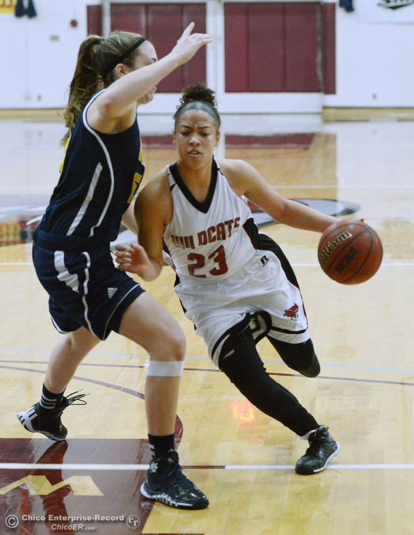 Description of . Chico State's #23 Jazmine Miller (right) dribbles against UC San Diego's #5 Cassie MacLeod (left) in the first half of their women's basketball game at CSUC Acker Gym Friday, February 7, 2014 in Chico, Calif.  (Jason Halley/Chico Enterprise-Record)