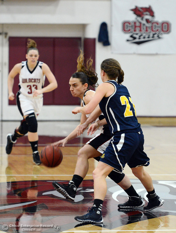 Description of . Chico State's #4 Sarah Rebibo (left) dribbles against UC San Diego's #21 Megan perry (right) in the first half of their women's basketball game at CSUC Acker Gym Friday, February 7, 2014 in Chico, Calif.  (Jason Halley/Chico Enterprise-Record)