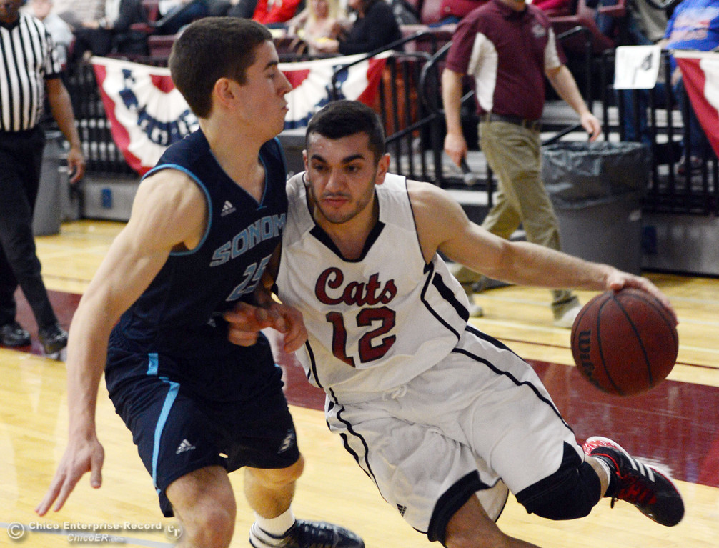 Description of . Chico State's #12 Giordano Estrada (right) dribbles against Sonoma State's #25 David Ahern (left) in the first half of their men's basketball game at CSUC Acker Gym Friday January 31, 2014 in Chico, Calif. (Jason Halley/Chico Enterprise-Record)