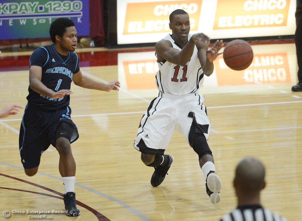 Description of . Chico State's #11 Rashad Parker (right) passes against Sonoma State's #1 Khalid Johnson (left) in the first half of their men's basketball game at CSUC Acker Gym Friday January 31, 2014 in Chico, Calif. (Jason Halley/Chico Enterprise-Record)