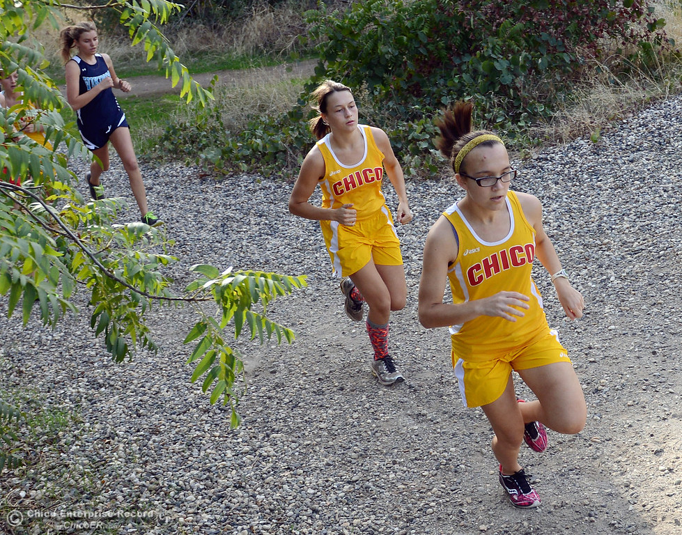 Description of . Chico High's Alyson Lacko (right) followed by Malene Kavanagh (left) lead the pack against Pleasant Valley High varsity girls cross country race at Hooker Oak Wednesday, October 2, 2013, in Chico, Calif.  (Jason Halley/Chico Enterprise-Record)