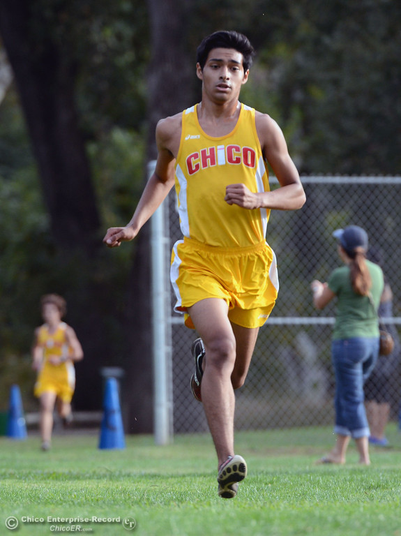 Description of . Chico High's Hector Damian-Sirodia finishes against Pleasant Valley High varsity boys cross country race at Hooker Oak Wednesday, October 2, 2013, in Chico, Calif.  (Jason Halley/Chico Enterprise-Record)