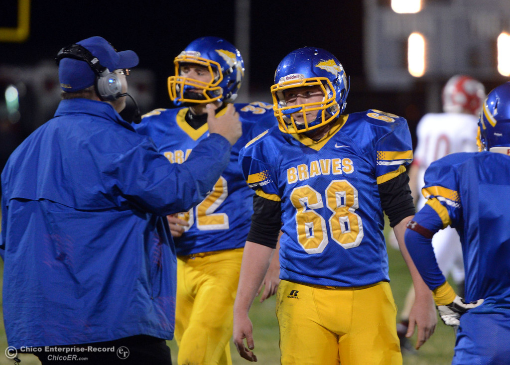 Description of . Hamilton High\'s coach Ryan Bentz (left) talks to #68 Riley Meridith(right) against Winters High in the first quarter of their football game at HHS Wednesday, November 27, 2013 in Hamilton City, Calif.  (Jason Halley/Chico Enterprise-Record)