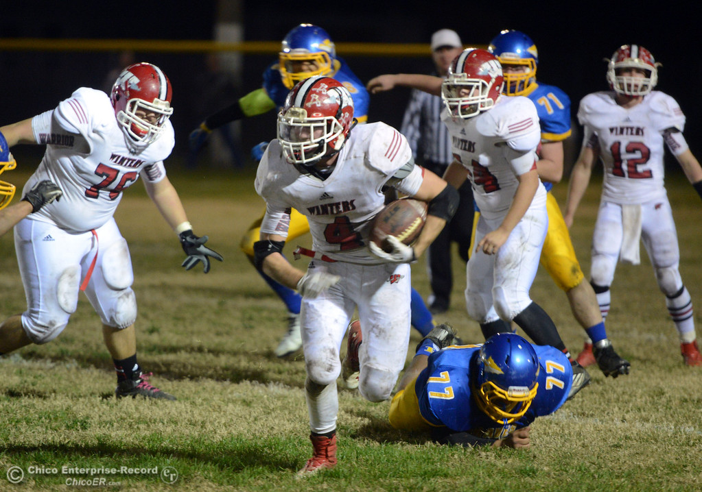 Description of . Winters High\'s #4 Chaz Matthews (center) rushes against Hamilton High\'s in the third quarter of their football game at HHS Wednesday, November 27, 2013 in Hamilton City, Calif.  (Jason Halley/Chico Enterprise-Record)