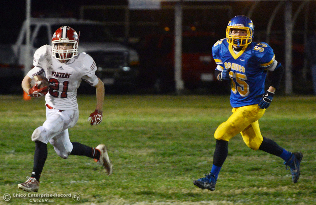 Description of . Winters High\'s #21 Trevor Ray (left) rushes against Hamilton High\'s #55 Chad Young (right) in the fourth quarter of their football game at HHS Wednesday, November 27, 2013 in Hamilton City, Calif.  (Jason Halley/Chico Enterprise-Record)
