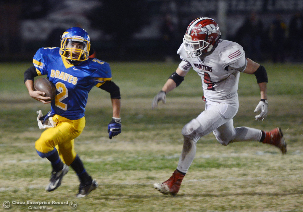 Description of . Hamilton High\'s #2 Theron Fumasi (left) rushes against Winters High\'s #4 Chaz Matthews (right) in the third quarter of their football game at HHS Wednesday, November 27, 2013 in Hamilton City, Calif.  (Jason Halley/Chico Enterprise-Record)