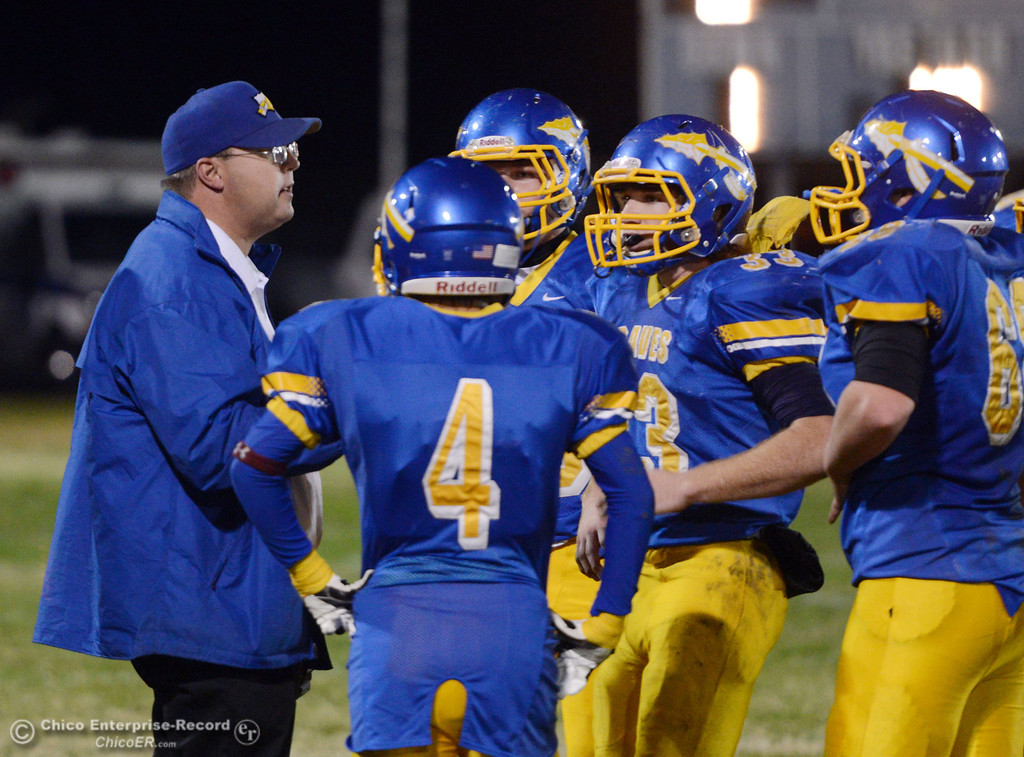 Description of . Hamilton High\'s coach Ryan Bentz (left) talks to the team against Winters High in the first quarter of their football game at HHS Wednesday, November 27, 2013 in Hamilton City, Calif.  (Jason Halley/Chico Enterprise-Record)