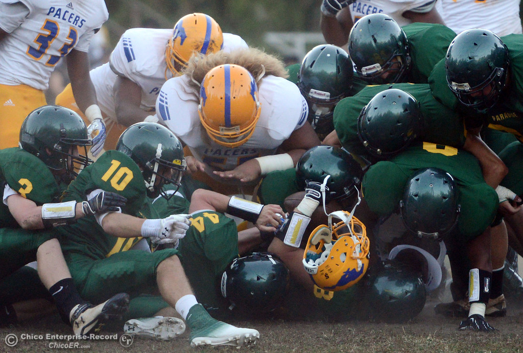 Description of . Paradise High's defense piles on a tackle against Grant High who has a helmet knocked loose in the first quarter of their football game at PHS Friday, August 30, 2013 in Paradise, Calif.  (Jason Halley/Chico Enterprise-Record)