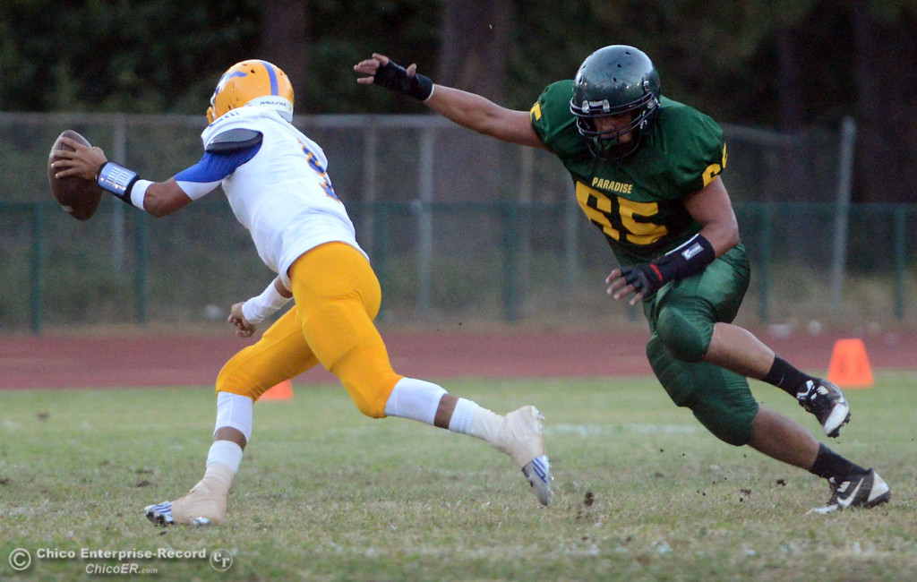 Description of . Paradise High's #65 Cameron Williams (right) defends against Grant High's #9 Donovan Brown (left) in the first quarter of their football game at PHS Friday, August 30, 2013 in Paradise, Calif.  (Jason Halley/Chico Enterprise-Record)