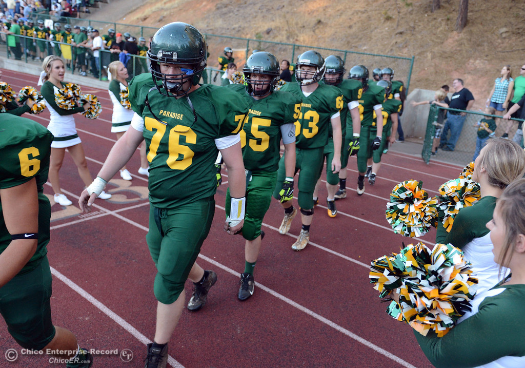 Description of . Paradise High's #76 Alex Wood, #55 Mike Comerate, and #63 Jesse Ballou (left to right) enter the field against Grant High before the first quarter of their football game at PHS Friday, August 30, 2013 in Paradise, Calif.  (Jason Halley/Chico Enterprise-Record)
