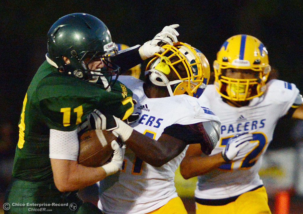 Description of . Paradise High's #11 DJ Norton (left) puts up a stiff arm against Grant High's #21 Ben Johnson (center) as #12 Chris Atteberry (right) looks on during the second quarter of their football game at PHS on Friday, August 30, 2013 in Paradise, Calif.  (Jason Halley/Chico Enterprise-Record)
