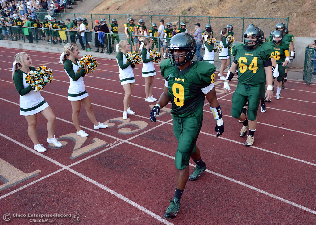 Description of . Paradise High's #9 Jonathon Dixon (left) and #64 Caleb Anderson (right) enter the field against Grant High before the first quarter of their football game at PHS Friday, August 30, 2013 in Paradise, Calif.  (Jason Halley/Chico Enterprise-Record)