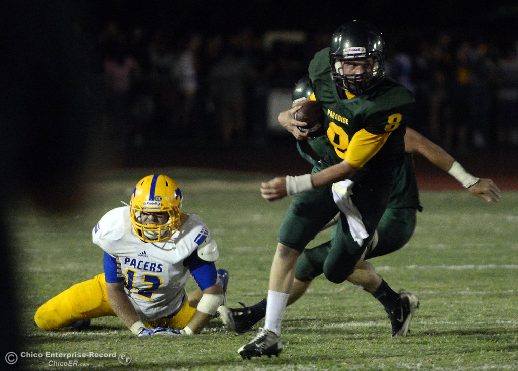 . Paradise High\'s #8 Kenny Bengson (right) breaks the tackle against Grant High\'s #12 Chris Atteberry (left) during the second quarter of their football game at PHS on Friday, August 30, 2013 in Paradise, Calif.  (Jason Halley/Chico Enterprise-Record)