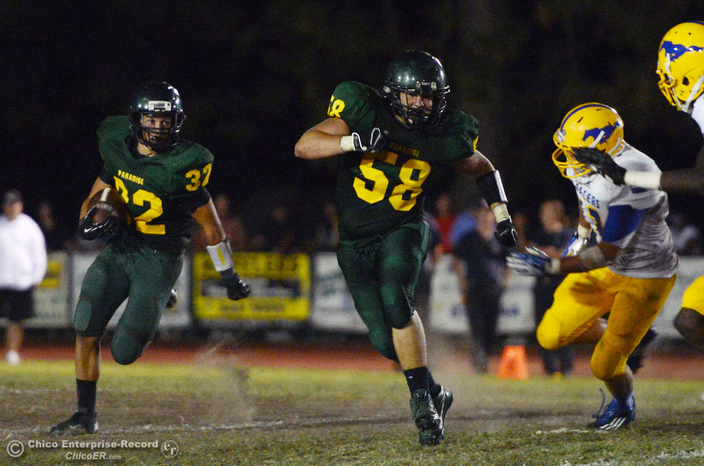 . Paradise High\'s #32 Nick Klein (left) rushes behind #58 Nate McFarland (right) against Grant High in the third quarter of their football game at PHS Friday, August 30, 2013 in Paradise, Calif.  (Jason Halley/Chico Enterprise-Record)