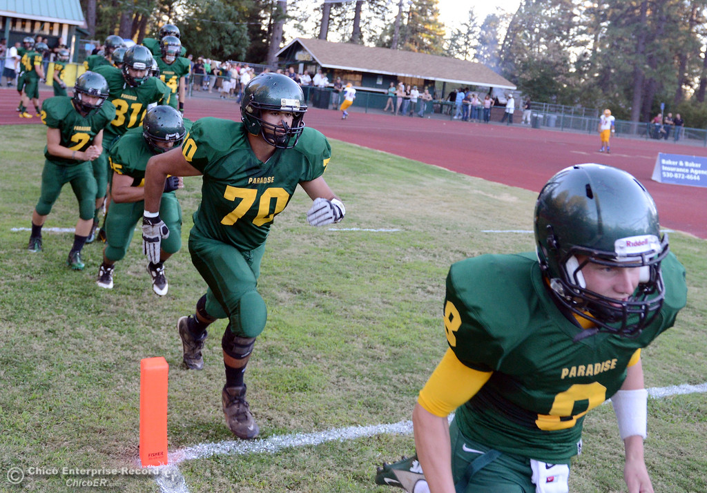 Description of . Paradise High's #8 Kenny Bengson (right) and #70 Daniel Garcia (center) enter the field against Grant High before the first quarter of their football game at PHS Friday, August 30, 2013 in Paradise, Calif.  (Jason Halley/Chico Enterprise-Record)