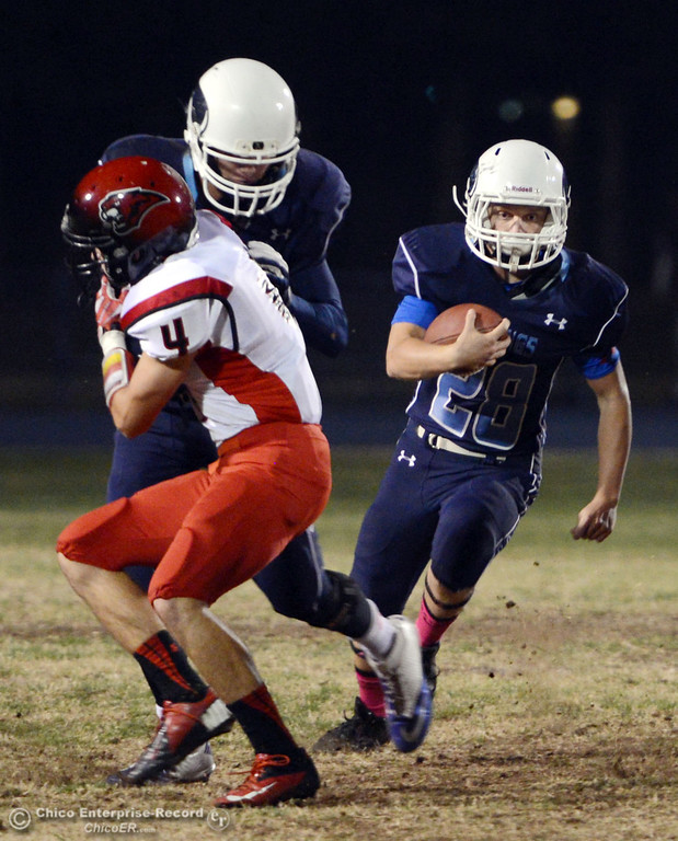 Description of . Pleasant Valley High\'s #28 Dylan Batie (right) rushes on a block by #25 Ryan Steindorf (center) against Foothill High\'s #4 Luke Kelly (left) in the first quarter of their football game at PVHS Asgard Yard Friday, October 11, 2013 in Chico, Calif.  (Jason Halley/Chico Enterprise-Record)