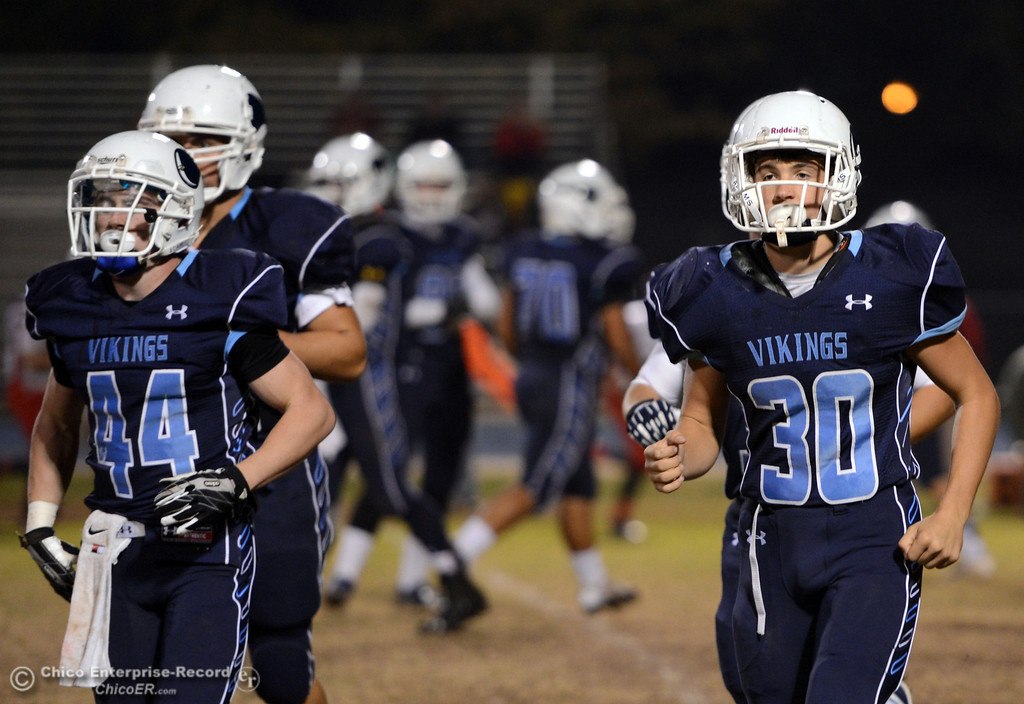 Description of . Pleasant Valley High\'s #44 Cyland Leitner (left) and #30 Connor Melton (right) come off the field against Foothill High in the first quarter of their football game at PVHS Asgard Yard Friday, October 11, 2013 in Chico, Calif.  (Jason Halley/Chico Enterprise-Record)
