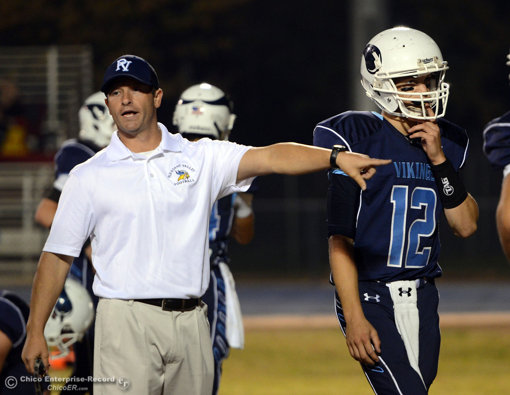 Description of . Pleasant Valley High head coach Mark Cooley (left) with #12 Trent Darms (right) runs drills against Foothill High before the first quarter of their football game at PVHS Asgard Yard Friday, October 11, 2013 in Chico, Calif.  (Jason Halley/Chico Enterprise-Record)