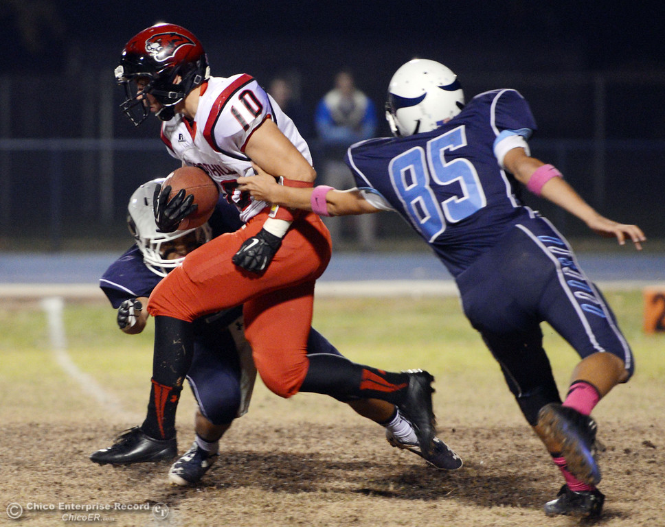 Description of . Pleasant Valley High\'s #3 Brandon Romero (left) and #10 Tucker LaRue (right) attempt to tackle against Foothill High\'s #10 Blake Burnett (center) in the first quarter of their football game at PVHS Asgard Yard Friday, October 11, 2013 in Chico, Calif.  (Jason Halley/Chico Enterprise-Record)