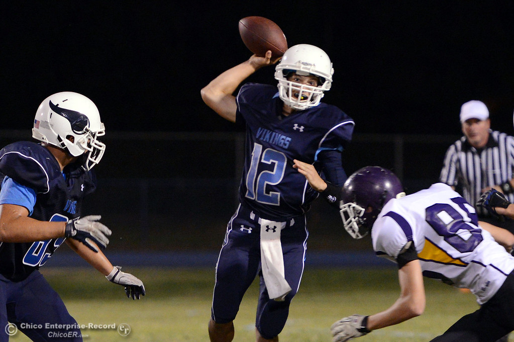 Description of . Pleasant Valley High's #12 Trent Darms throws under pressure against Lassen High in the second quarter of their football game at PVHS Asgard Yard Friday, September 6, 2013 in Chico, Calif. (Jason Halley/Chico Enterprise-Record)