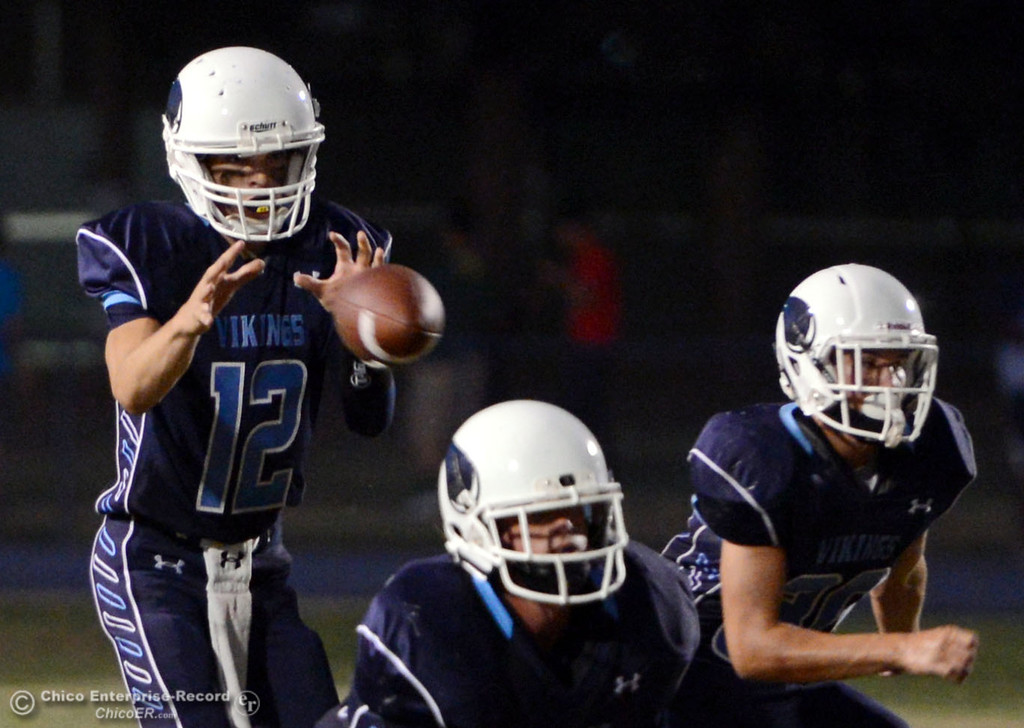 Description of . Pleasant Valley High's #12 Trent Darms takes a snap against Lassen High in the first quarter of their football game at PVHS Asgard Yard Friday, September 6, 2013 in Chico, Calif. (Jason Halley/Chico Enterprise-Record)