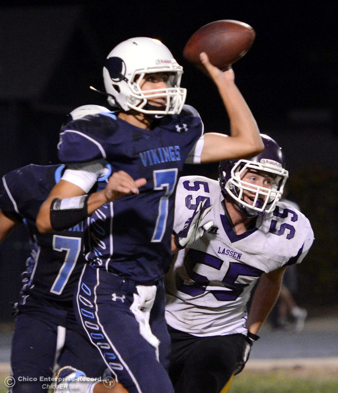 Description of . Pleasant Valley High's #7 Zane Ferguson (left) passes against Lassen High's #55 Colton Faure (right) in the fourth quarter of their football game at PVHS Asgard Yard Friday, September 6, 2013 in Chico, Calif. (Jason Halley/Chico Enterprise-Record)