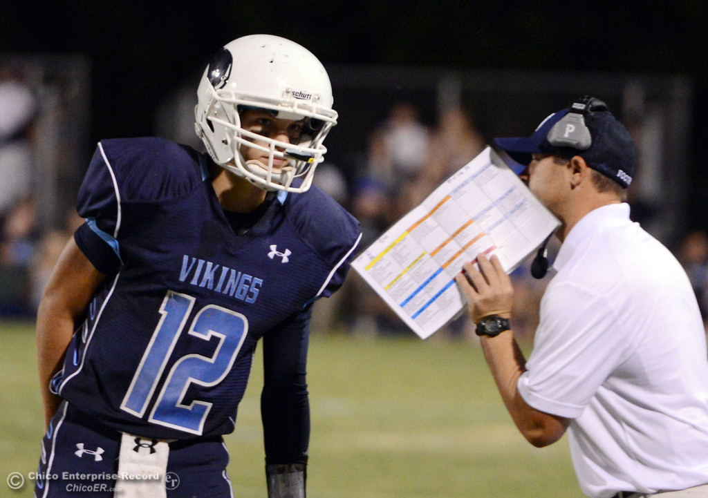 Description of . Pleasant Valley High's #12 Trent Darms (left) gets the play from coach Mark Cooley (right) against Lassen High in the second quarter of their football game at PVHS Asgard Yard Friday, September 6, 2013 in Chico, Calif. (Jason Halley/Chico Enterprise-Record)