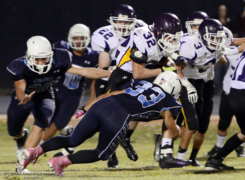 Description of . Pleasant Valley High's #33 Taylor Wright (bottom) tackles against Lassen High's #32 Skyler Ingwerson (top) in the third quarter of their football game at PVHS Asgard Yard Friday, September 6, 2013 in Chico, Calif. (Jason Halley/Chico Enterprise-Record)