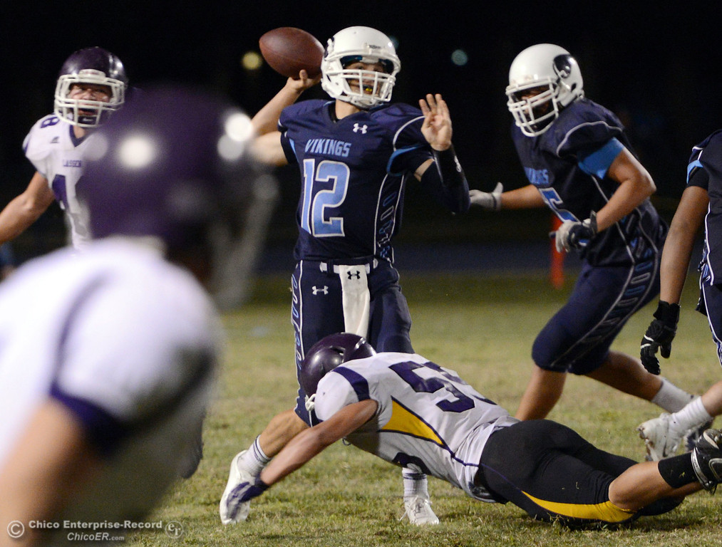 Description of . Pleasant Valley High's #12 Trent Darms throws under pressure against Lassen High in the fourth quarter of their football game at PVHS Asgard Yard Friday, September 6, 2013 in Chico, Calif. (Jason Halley/Chico Enterprise-Record)
