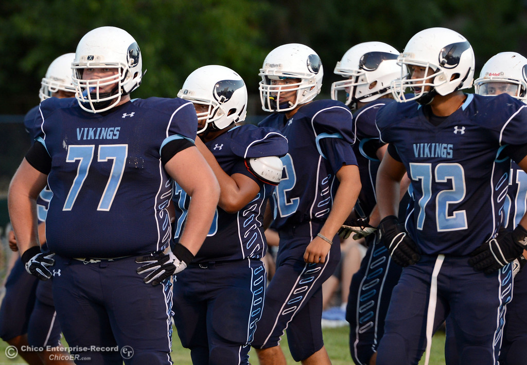 Description of . Pleasant Valley High's #77 Tyler Stimac (left) and #72 Christian Darden (right) warm up against Lassen High before the first quarter of their football game at PVHS Asgard Yard Friday, September 6, 2013 in Chico, Calif. (Jason Halley/Chico Enterprise-Record)