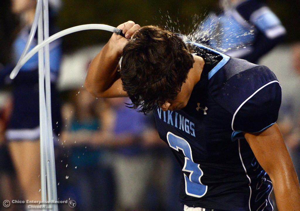 Description of . Pleasant Valley High's #3 Brandon Romero pours water on his neck against Lassen High in the second quarter of their football game at PVHS Asgard Yard Friday, September 6, 2013 in Chico, Calif. (Jason Halley/Chico Enterprise-Record)