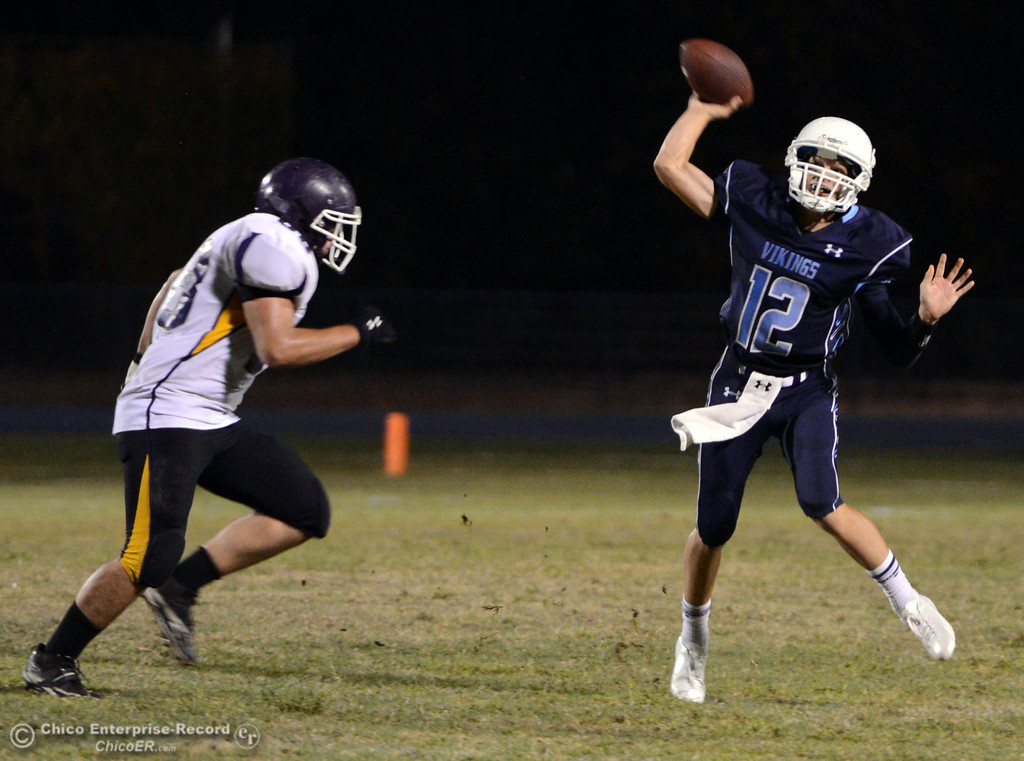 Description of . Pleasant Valley High's #12 Trent Darms (right) throws a pass against Lassen High's #68 Jacob Gregg (left) in the second quarter of their football game at PVHS Asgard Yard Friday, September 6, 2013 in Chico, Calif. (Jason Halley/Chico Enterprise-Record)