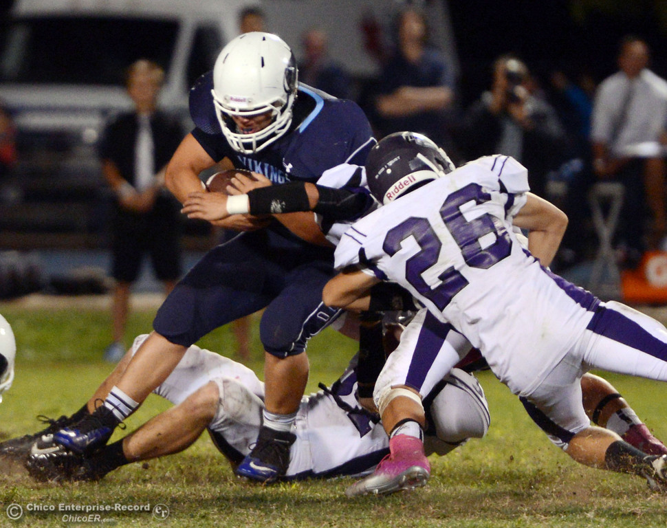 Description of . Pleasant Valley High\'s #9 Houston McGowan (left) is tackled against Oroville High\'s #26 Dylan Shoemaker (right) and #34 Thomas Miller (bottom) in the third quarter of their football game at PVHS Asgard Yard Friday, September 20, 2013, in Chico, Calif. (Jason Halley/Chico Enterprise-Record)