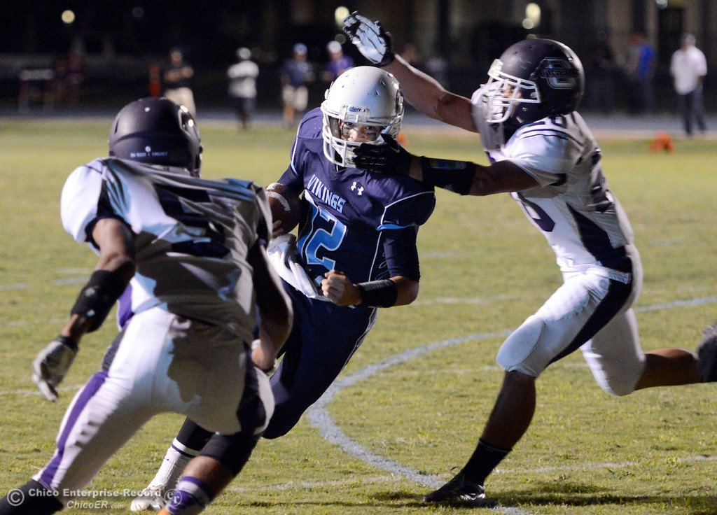 Description of . Pleasant Valley High\'s #12 Trent Darms (left) breaks tackles to rush for a touchdown against Oroville High\'s #5 Kahiel Wyatt (left) and #20 Brandon Tewksbury (right) in the second quarter of their football game at PVHS Asgard Yard Friday, September 20, 2013, in Chico, Calif. (Jason Halley/Chico Enterprise-Record)