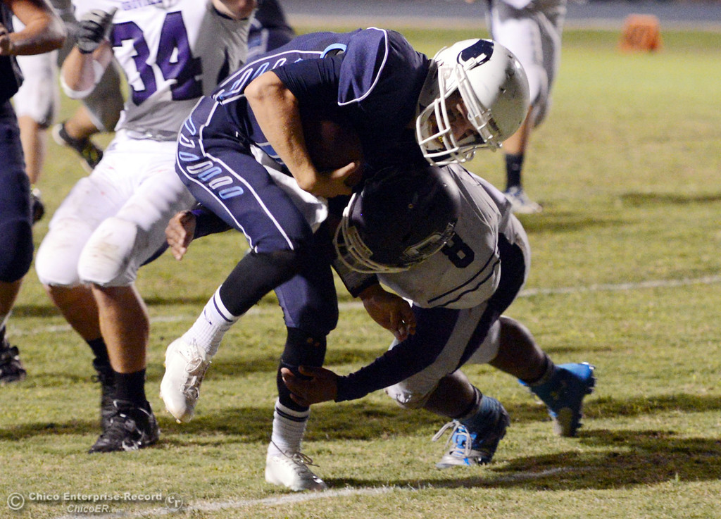 Description of . Pleasant Valley High\'s #12 Trent Darms (left) is tackled against Oroville High\' #8 James Jones (right) in the second quarter of their football game at PVHS Asgard Yard Friday, September 20, 2013, in Chico, Calif. (Jason Halley/Chico Enterprise-Record)