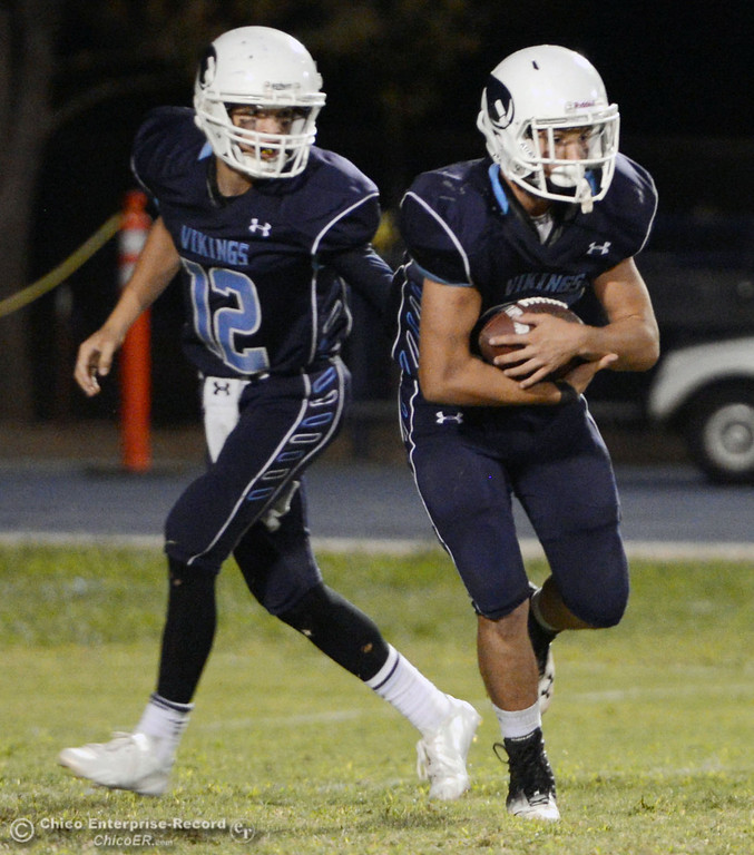 Description of . Pleasant Valley High\'s #12 Trent Darms (left) hands off to #30 Connor Melton (right) against Oroville High in the third quarter of their football game at PVHS Asgard Yard Friday, September 20, 2013, in Chico, Calif. (Jason Halley/Chico Enterprise-Record)
