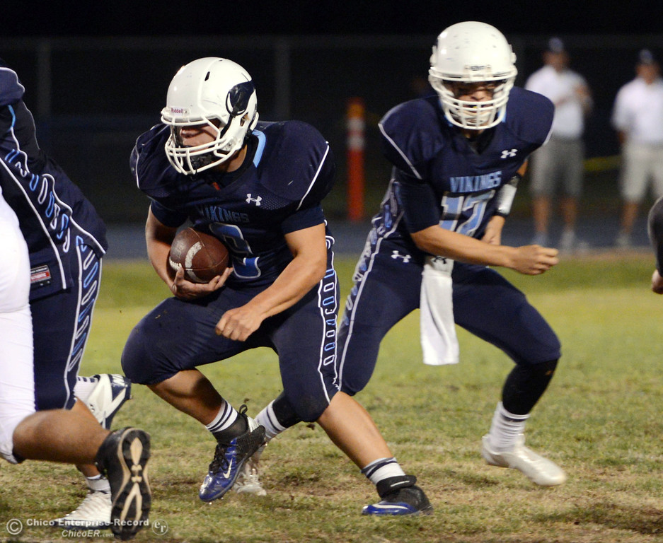 Description of . Pleasant Valley High\'s #9 Houston McGowan (left) receives the handoff from #12 Trent Darms (right) against Oroville High in the first quarter of their football game at PVHS Asgard Yard Friday, September 20, 2013, in Chico, Calif. (Jason Halley/Chico Enterprise-Record)