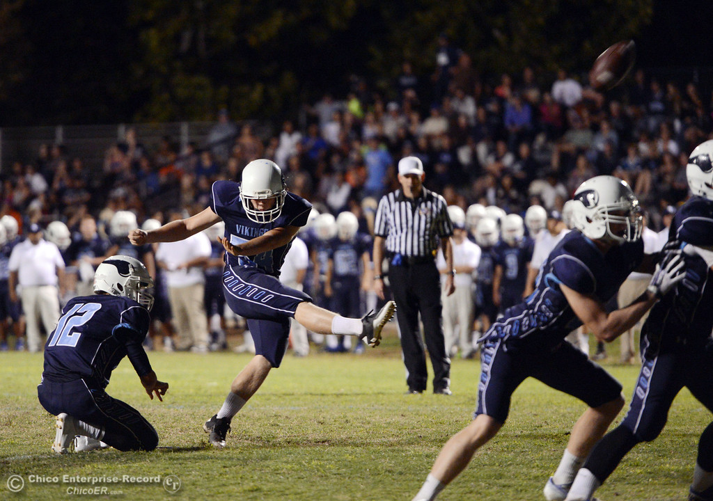 Description of . Pleasant Valley High\'s #12 Trent Darms (left) holds for #54 Zack GIlam to kick the extra point against Oroville High in the third quarter of their football game at PVHS Asgard Yard Friday, September 20, 2013, in Chico, Calif. (Jason Halley/Chico Enterprise-Record)