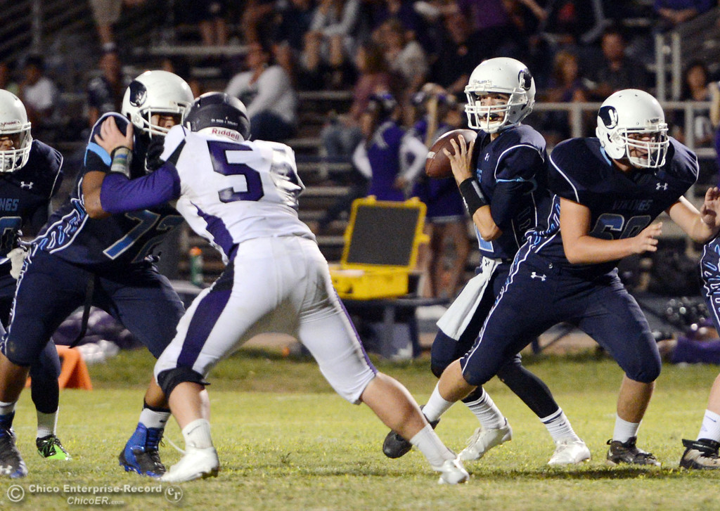 Description of . Pleasant Valley High\'s #12 Trent Darms drops back to pass against Oroville High in the second quarter of their football game at PVHS Asgard Yard Friday, September 20, 2013, in Chico, Calif. (Jason Halley/Chico Enterprise-Record)