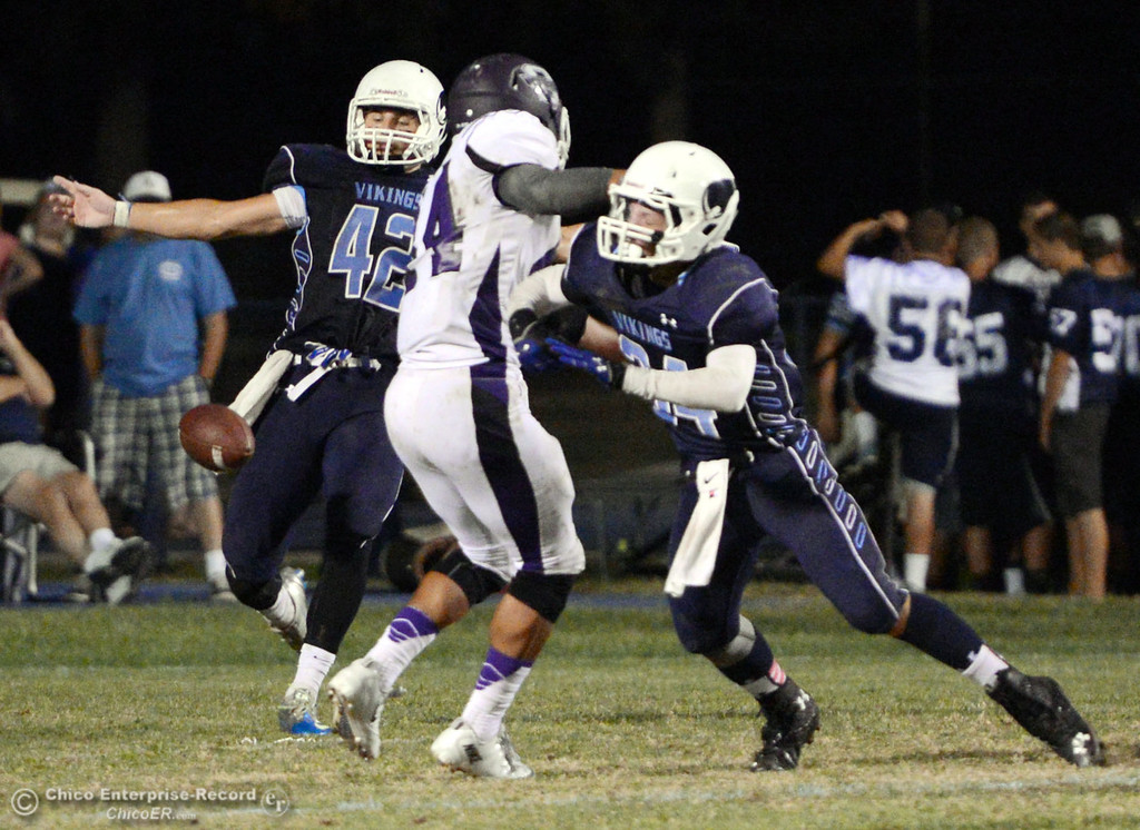 Description of . Pleasant Valley High\'s #42 Chad Olsen (left) punts from a block of #34 Cale Crawford (right) against Oroville High\'s #44 Derrek Gordon (center) in the second quarter of their football game at PVHS Asgard Yard Friday, September 20, 2013, in Chico, Calif. (Jason Halley/Chico Enterprise-Record)