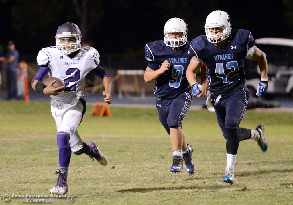 Description of . Oroville High\'s #2 Marcus WIlhite (left) rushes against Pleasant Valley High\'s #9 Houston McGowan (center) and #42 Chad Olsen (right) in the fourth quarter of their football game at PVHS Asgard Yard Friday, September 20, 2013, in Chico, Calif. (Jason Halley/Chico Enterprise-Record)