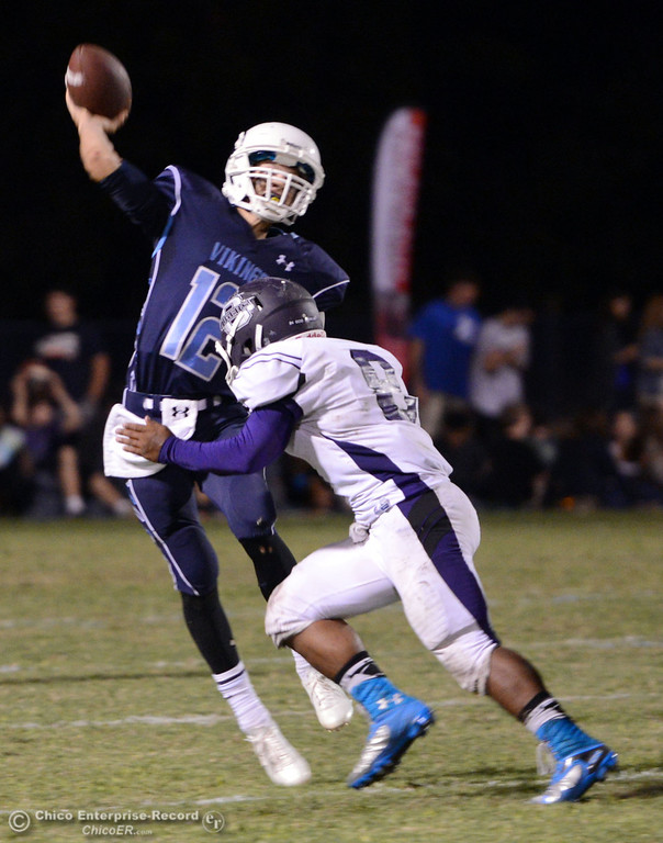 Description of . Pleasant Valley High\'s #12 Trent Darms (left) is pressured against Oroville High\'s #8 James Jones (right) in the third quarter of their football game at PVHS Asgard Yard Friday, September 20, 2013, in Chico, Calif. (Jason Halley/Chico Enterprise-Record)