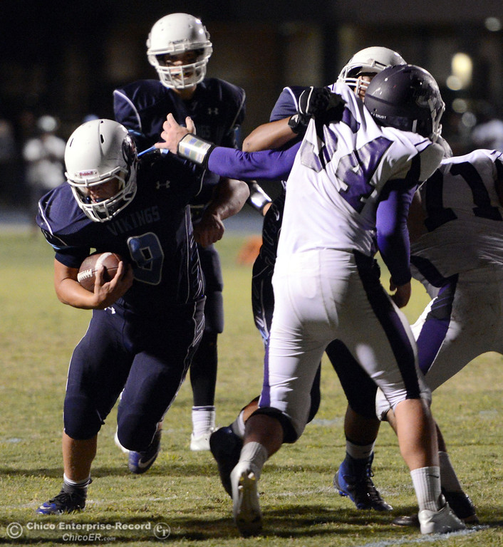 Description of . Pleasant Valley High\'s #9 Houston McGowan (center) rushes against Oroville High in the second quarter of their football game at PVHS Asgard Yard Friday, September 20, 2013, in Chico, Calif. (Jason Halley/Chico Enterprise-Record)