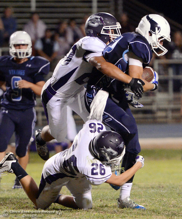 Description of . Pleasant Valley High\'s #42 Chad Olsen (right) is tackled against Oroville High\'s #20 Brandon Tewksbury (left) and #26 Dylan Shoemaker (bottom) in the first quarter of their football game at PVHS Asgard Yard Friday, September 20, 2013, in Chico, Calif. (Jason Halley/Chico Enterprise-Record)