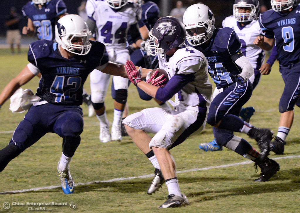 Description of . Oroville High\'s #4 Antony Ramsey (center) is tackled against Pleasant Valley High\'s #42 Chad Olsen (left) and #34 Cale Crawford (right) in the second quarter of their football game at PVHS Asgard Yard Friday, September 20, 2013, in Chico, Calif. (Jason Halley/Chico Enterprise-Record)
