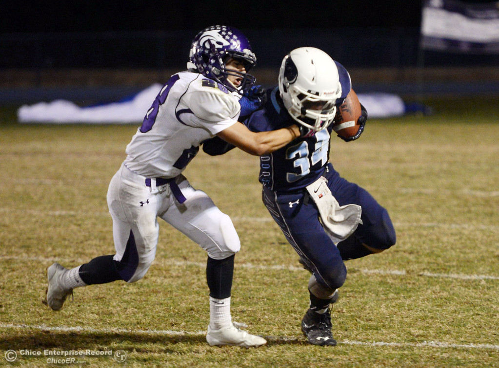 Description of . Pleasant Valley High\'s #34 Cale Crawford (right) is tackled against Shasta High\'s #28 Anthony Archuleta (left) in the second quarter of their football game at PVHS Asgard Yard Friday, October 18, 2013 in Chico, Calif.  (Jason Halley/Chico Enterprise-Record)