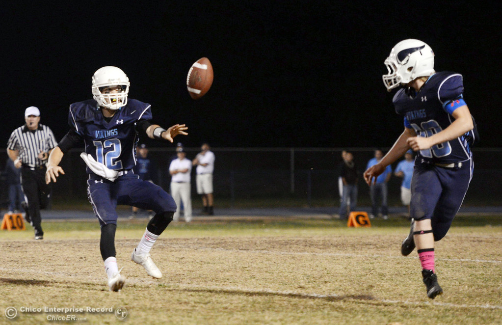 Description of . Pleasant Valley High\'s #12 Trent Darms (left) tosses the ball to #28 Dylan Batie (right) against Shasta High in the second quarter of their football game at PVHS Asgard Yard Friday, October 18, 2013 in Chico, Calif.  (Jason Halley/Chico Enterprise-Record)