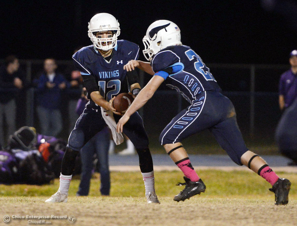 Description of . Pleasant Valley High\'s #12 Trent Darms (left) fakes a hand off to #28 Dylan Batie (right) against Shasta High in the second quarter of their football game at PVHS Asgard Yard Friday, October 18, 2013 in Chico, Calif.  (Jason Halley/Chico Enterprise-Record)