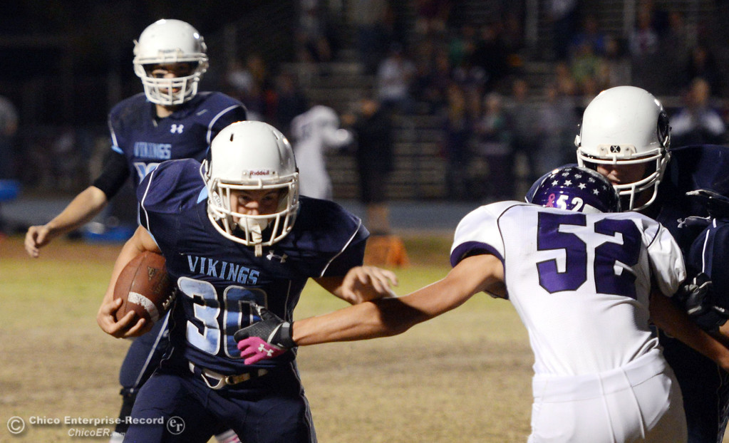 Description of . Pleasant Valley High\'s #30 Connor Melton (left) rushes against Shasta High\'s #52 Jake Thengvall (right) in the first quarter of their football game at PVHS Asgard Yard Friday, October 18, 2013 in Chico, Calif.  (Jason Halley/Chico Enterprise-Record)