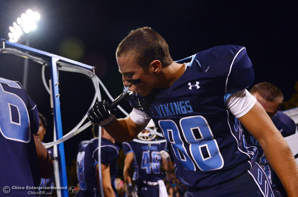 Description of . Pleasant Valley High\'s #88 Zack Suttles (right) takes a drink of water against Shasta High in the first quarter of their football game at PVHS Asgard Yard Friday, October 18, 2013 in Chico, Calif.  (Jason Halley/Chico Enterprise-Record)